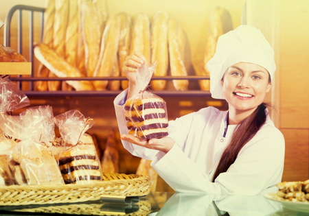 Portrait of friendly smiling charming woman at bakery display with pastry