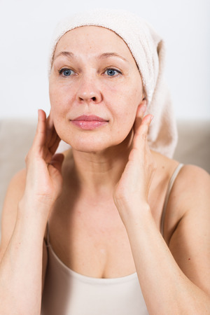 necessity: Elderly woman using face cream during beauty procedures at home Stock Photo