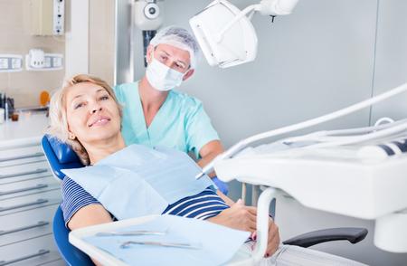 歯科医のオフィスでの歯科治療後の笑顔の女性患者が満足
