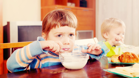 baby girls eating dairy breakfast at table in home interior