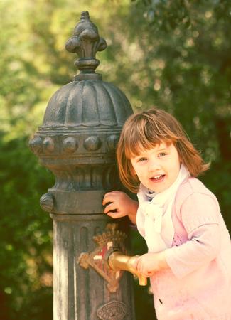 Baby girl using water pump on street of Barcelona, Spain