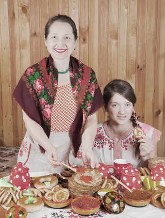 Happy mother with teenager daughter eating pancake with caviare during  Shrovetide photo