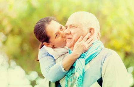 Mature couple kissing in autumn park photo