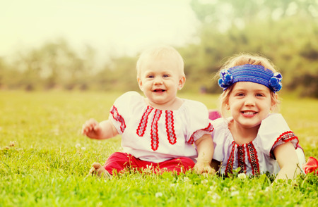 Two happy children in russian folk clothes on grass Stock Photo