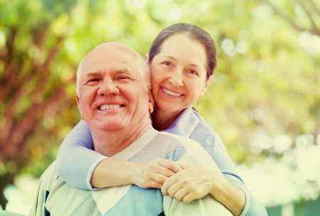 Portrait of cheerful mature couple together in autumn park photo