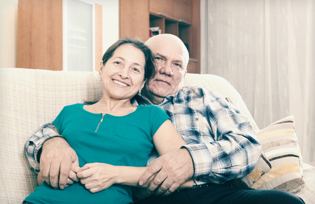 Portrait of laughing mature woman with elderly man in home interior photo