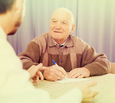 Old man and social department manager fill in questionnaire Stock Photo