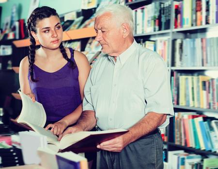 De blije oude man met meisje leest boeken in boekhandel