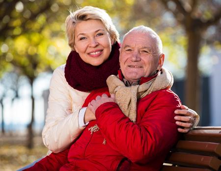 homme d & # 39 ; âge mûr et femme assise confortablement sur banc dans le parc