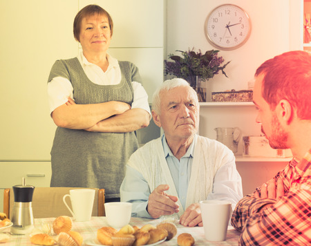 teaches: Elderly grandfather teaches his grandson in presence of grandmother Stock Photo