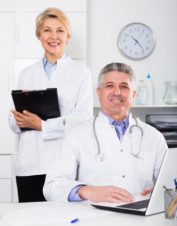 Médico y la enfermera en bata médica blanca espera para los pacientes de estancia en la mesa Foto de archivo - 83173701