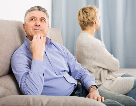 disappointed mature couple quarreling at home with each other and take offense
