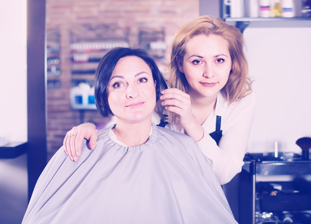 Woman is satisfied with work of haircutter and her hairdo in hairdress salon