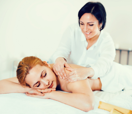 Adult smiling cheerful masseuse makes relaxing massage shoulder zone to young woman in beauty parlor