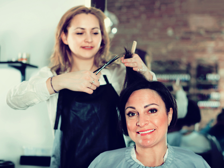 Young  cheerful positive hairdresser does to woman haircut with use of scissors and hairbrushes in hairdress salon