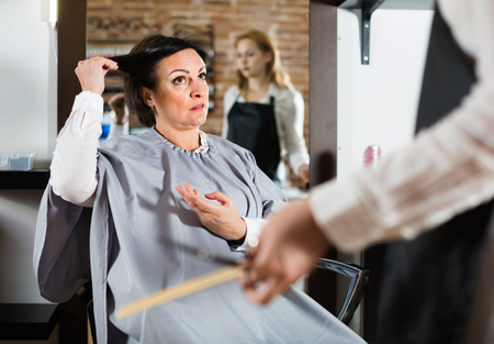 Unhappy  woman telling to young hairdresser that she does not like her hairstyle