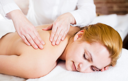 Young smiling woman is very pleased with procedure of massage in massage salon. Selective focus on hands