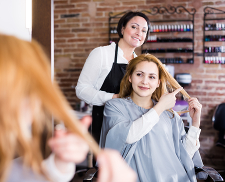 Adult woman points to hairdresser in hairdressing salon about necessary length of hair at haircut