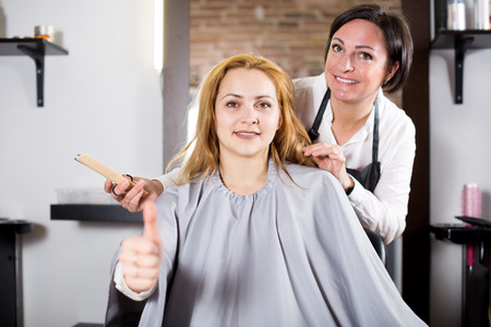 Smiling blonde woman is satisfied with work of master and her hairdo in hairdress salon