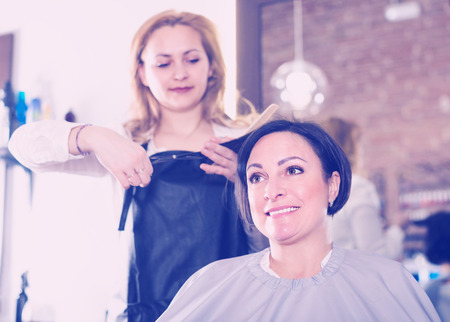 Hairdresser is doing hairstyle and cut by means of scissors and hairbrush for woman.