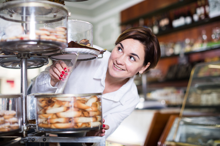 Young female client choosing delicious dessert in confectionery Stock Photo