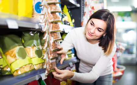 Young american woman choosing delicious snacks in supermarket