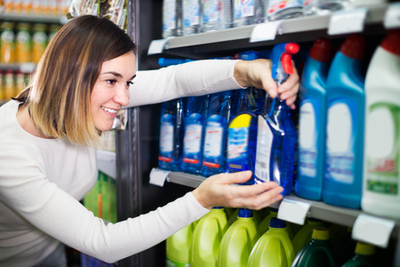 Glad female shopper searching for cleaners in supermarket