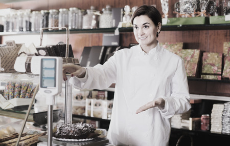 teacake: Smiling female seller weighing on scales festive chocolate cake in confectionery Stock Photo