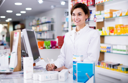 Smiling pharmacist ready to assist in choosing at counter in pharmacy Stockfoto