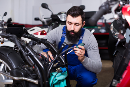 bearded man worker working at restoring motorbike in motorcycle workshop Stock Photo