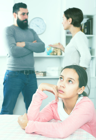 Young father and mother quarrelling with each other while their daughter at home