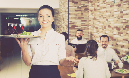Smiling female waiter greeting customers at table in restaurant Stock Photo