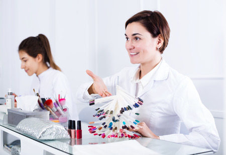 schemes: Pretty young woman doing nails displaying polish color schemes in nail salon Stock Photo
