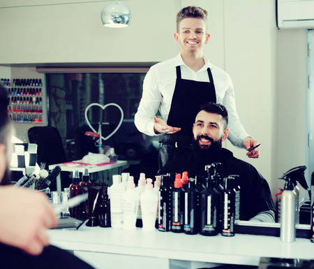 Smiling young hairdresser displaying result of work to client at hair salon Stock Photo
