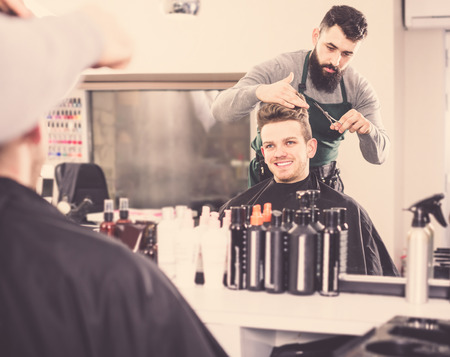 barbershop: Young guy stylist creating new haircut for man client at hairdressing salon