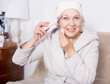 Senior woman starting face cleaning with ultrasonic device at home