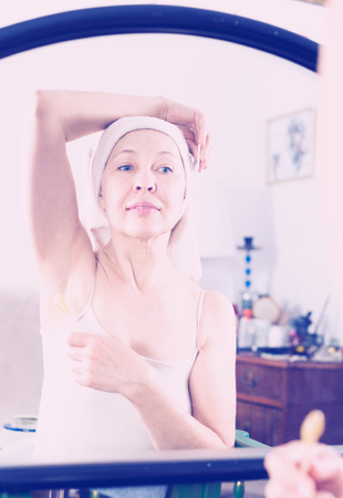 necessity: Senior woman starting body hair removal at home Stock Photo