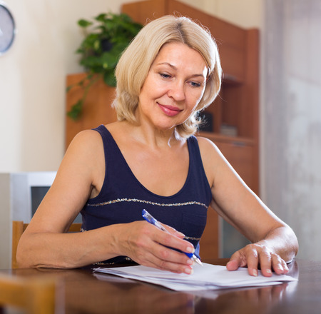 fifty something: Portrait of mature businesswoman with financial bill at home