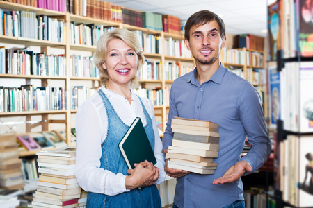 Smiling young man and mature woman holding books in hands in book store