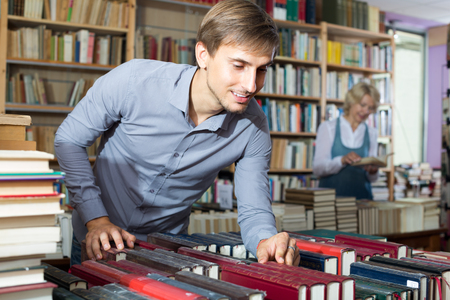 portrait of young  smiling man  in blue shirt standing among bookshelves and searching for book Stock Photo