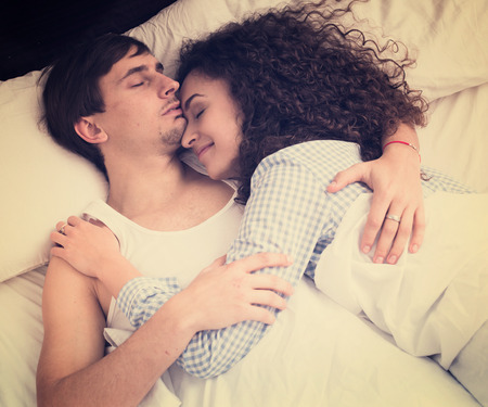Handsome young man with girlfriend sleeping and cuddling at home Stock Photo