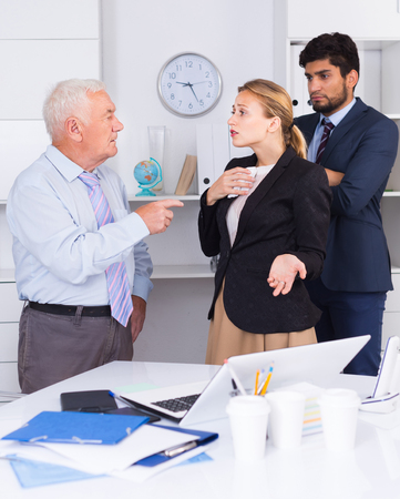 Old boss is chastising employees because of uncompleted work in the office.