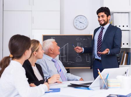 Manager männlich liest Finanzbericht auf Kollegen im Büro