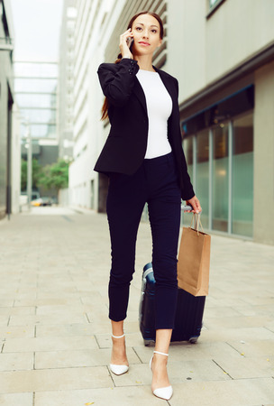 Female in suit with suitcase is talking by phone and going to the hotel.