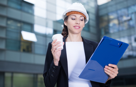 Female designer in suit and hat with folder is looking into documents with project and drinking coffee  near the building. Stock Photo