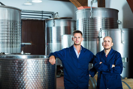 Portrait of two male coworkers standing on wine factory in secondary fermentation section