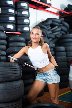 Glad technician girl working in car workshop indoors