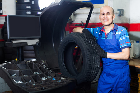 Mature happy male technician holding car wheel ready to work with balancing machinery at workshop Stock Photo