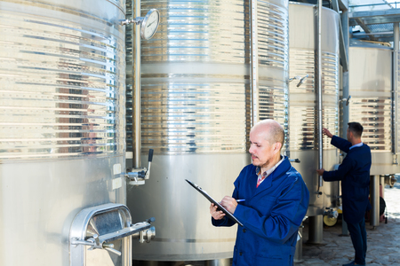 portrait of mature man wearing coat standing and taking off data from equipment in winery