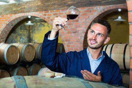 Cheerful male winemaker in uniform having glass of wine in hands in cellar Stock Photo
